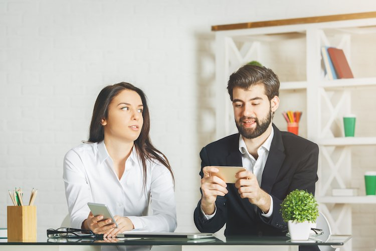 Two employees being distracted by smartphones in the office environment