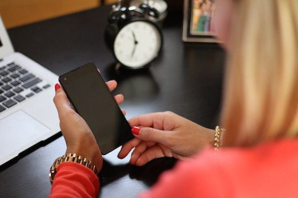 A female employee using her cell phone at work, distracted from her tasks